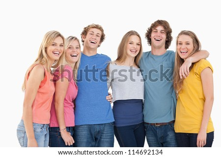 A group of friends holding each other and smiling while looking into the camera