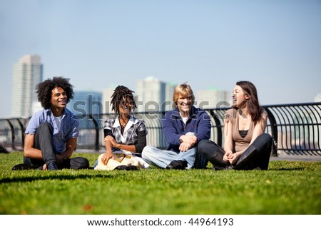 A group of friends in a city park talking and laughing