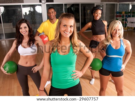 a group of friends in a fitness class using medicine balls