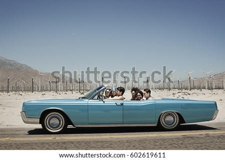 A group of friends in a pale blue convertible on the open road, driving across a dry flat plain surrounded by mountains #602619611