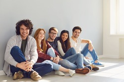 A group of friends is sitting on the floor in a room on a gray background.