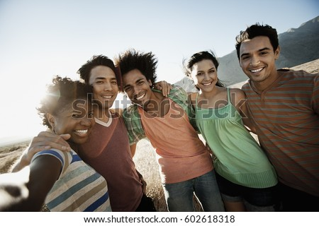 A group of friends, men and women, heads together posing for a selfy in the heat of the day