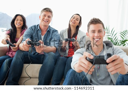 A group of friends playing games and laughing sit in front of the camera