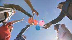 A group of friends release colorful balloons into the sky.