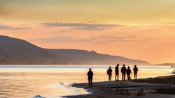 A group of friends walks along a sandy beach against the background of the Volga River and the Zhiguli Mountains at evening sunset.