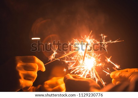 A group of friends who held a party and smiled happily at sparklers. #1129230776