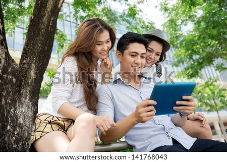 A group of friends with a tablet outside