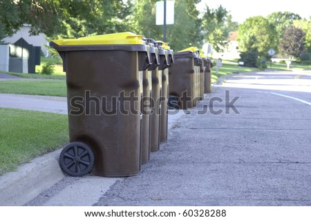 A group of Garbage cans on the side of the road