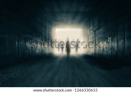 A group of ghostly figures emerging from the light at the end of a dark sinister tunnel. With a high contrast edit. Stock photo ©