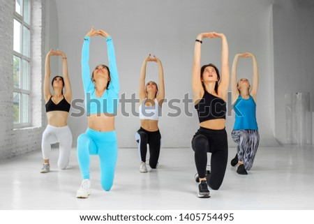 A group of girls doing aerobics in the gym. The concept of sports, a healthy lifestyle, fitness, stretching and dancing.