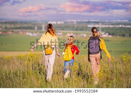 A group of girls walking in nature, running towards the city far on the horizon