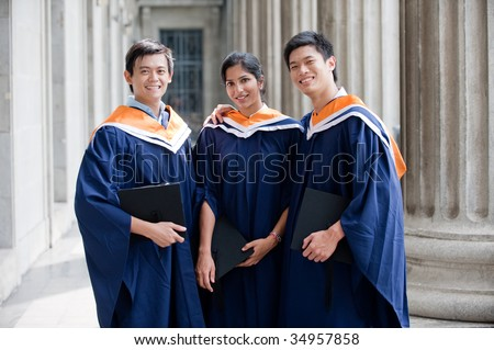 A group of graduates holding their mortar board in their hands and standing in a hallway