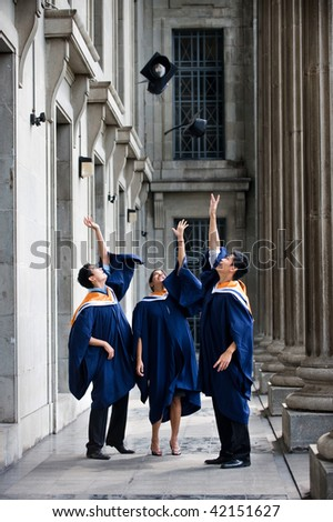 A group of graduates toss their mortar boards into the air in a hallway