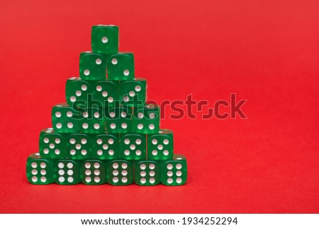 A group of green cubes lies in the form of a pyramid or stacks in ascending order on a red background of the text space: a Christmas tree made of green game cubes Stock photo ©