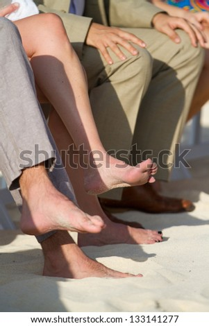A group of guests sitting with the feet in the sand at a beach wedding