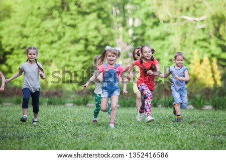 A group of happy children of boys and girls run in the Park on the grass on a Sunny summer day . The concept of ethnic friendship, peace, kindness, childhood #1352416586