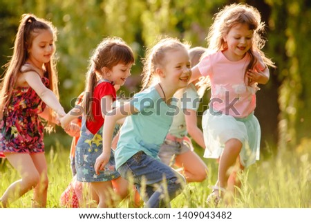 A group of happy children of boys and girls run in the Park on the grass on a Sunny summer day . The concept of ethnic friendship, peace, kindness, childhood #1409043482