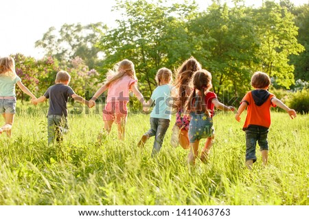 A group of happy children of boys and girls run in the Park on the grass on a Sunny summer day . The concept of ethnic friendship, peace, kindness, childhood #1414063763