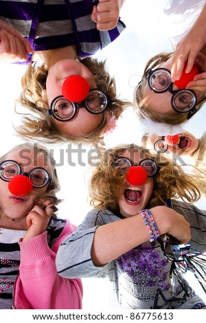 A group of happy children wearing clown noses and silly glasses looking down on the camera.