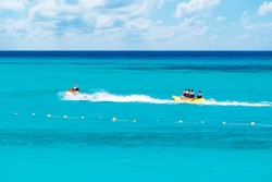 A Group of Happy People Riding Banana Boat Under Sunlight with Blue Sea Water in Background, Sharm El Sheikh, Sinai, Egypt