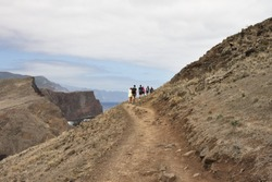 A group of hikers are walking along a desert pathway with volcanic rocks and sand dunes in Madeira Island (Ponta de Sao Lourenco, Portugal, Europe)
