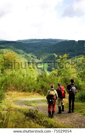 A group of hikers enjoying the view over the Ardennes mountains in the late summer.