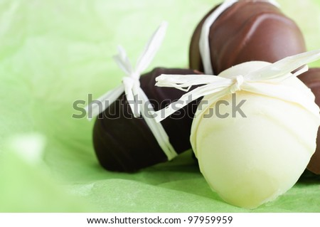 A group of home made Easter egg chocolates, bow tied with raffia ribbon, nestling on a fresh, light Spring green background.  Copy space to left.