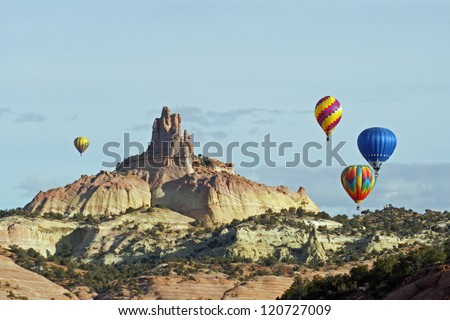 A group of hot air balloons rise above the red sandstone of Red Rocks State Park near Gallup, New Mexico, and circle around the Church Rock formation
