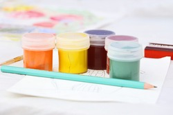 A group of jars with multicolored gouache.Pencil on the front.Concepft of the child art and painting.