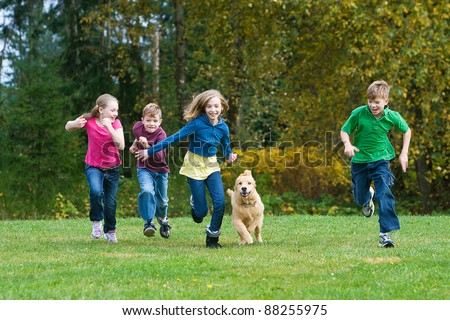 A group of 4 kids racing in a park with a dog.