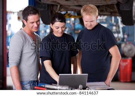 A group of mechanics referring to a laptop for service order or diagnostics results