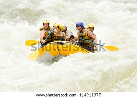 A group of men and women, with a guide, white water rafting on the Pastaza river, Ecuador