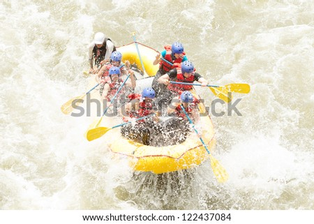 A group of men and women, with a guide, white water rafting on the Patate river, Ecuador