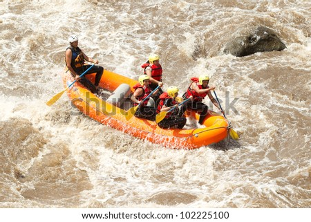 A GROUP OF MEN AND WOMEN, WITH A GUIDE, WHITEWATER RAFTING ON THE PATATE RIVER, ECUADOR