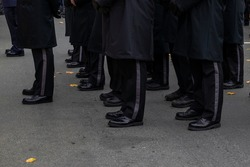 A group of men standing at attention in black suites on parade. The men are wearing military dress uniforms. The footwear is black shiny boots.  The military soldiers are lined up in rows on pavement.