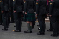 A group of men standing at attention in black suits and a kilt on parade. The men are wearing military dress uniforms. The footwear is black shiny boots.
