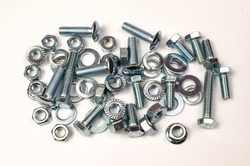 A group of metal products, bolts, nuts, washers is shot close-up. Details are stacked in a small pile.