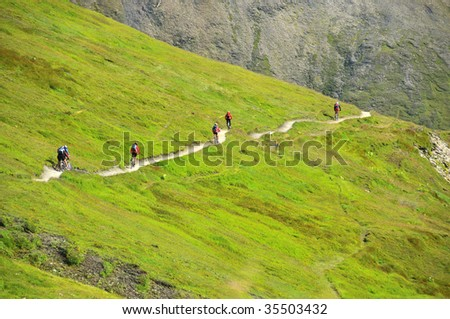 a group of mountain bikers on a path in the mountains on the tour de mont blanc