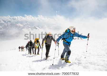 A group of mountaineers climbs to the top of a snow-capped mountain #700077832