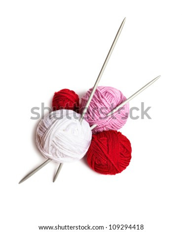 a group of multi-colored balls of yarn and knitting needles on a white background