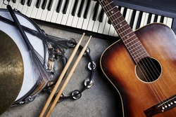 a group of musical instruments including a guitar, drum, and keyboard