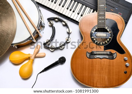 a group of musical instruments including a guitar, drum, keyboard, tambourine. #1081991300