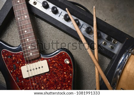 a group of musical instruments including an electric guitar, drum, cymbal, and amplifier #1081991333