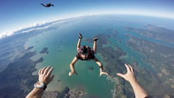 A group of parachuting friends jumping over the sea. First person view.