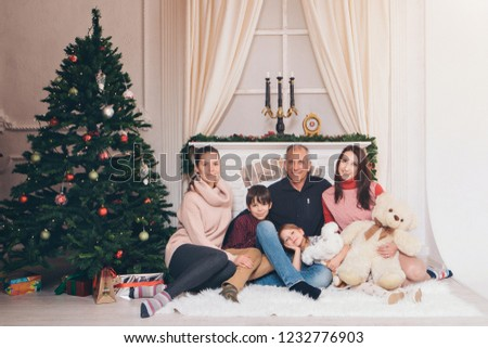 a group of 7 people and one Teddy: a large family sitting on the floor against the fireplace, Christmas decorations, Christmas trees, clocks, candelabra