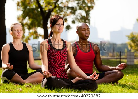 A group of people doing yoga in a city park - stock photo