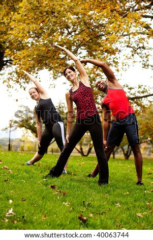 A group of people exercising in a park