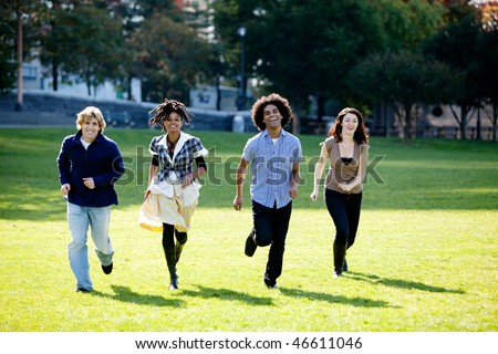 A group of people in a park, running towards the camera - stock photo