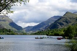 A group of people kayaking on Llyn Padarn Lake with Dolbadarn Castle in the background, part of the Snowdonia National Park, north Wales UK