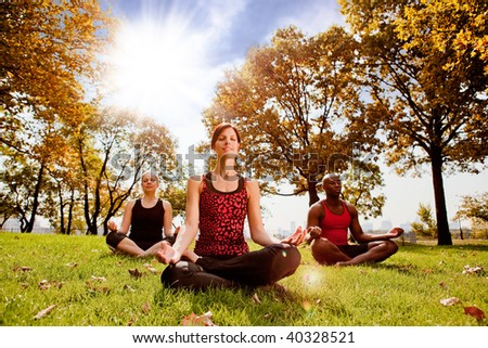 A group of people meditation in a city park in the morning - taken into the sun with lens flare